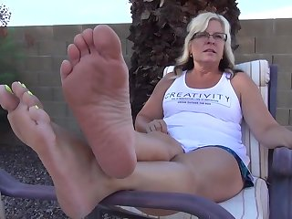 Good looking MILF exposing her tattooed feet with yellow nail polish outdoors