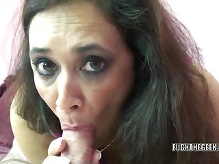 Mature swinger Alesia Pleasure lies on her belly while she swallows a stiff cock