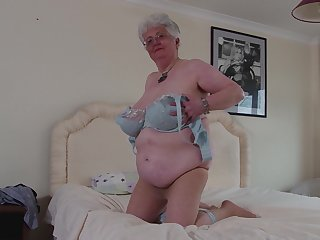 Mature buxom grey haired granny Caroline V. masturbates