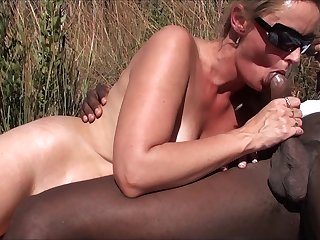 Blowing a big black prick outdoors